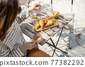 Cheerful woman sitting at a table in the garden. 77382292
