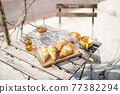 Croissants under the glass cloche with cups of coffee 77382294