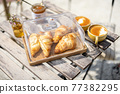 Croissants under the glass cloche with cups of coffee 77382295