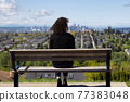 Adult Middle Age Woman sitting outside in a park 77383048