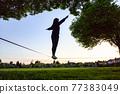 Adventurous White Caucasian Adult Woman walking on a Slackline 77383049