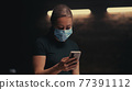Woman in mask making video call in dark room 77391112