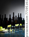 Shots of tequila with salt and lime. 77395161