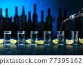 Shots of tequila with lime slices. 77395162