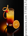 Cocktail tequila sunrise on a black reflective background. 77395171