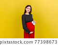 Happy pregnant woman holding baby girl booties against her belly at Colored background. Happy pregnancy. Copy space 77398673