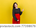 Happy pregnant woman showing thumb up cool gesture over her baby bump at Colored background. Happy maternity. Copy space 77398676