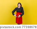 Pregnant woman scratching her belly on colored background 77398678