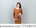 Happy pregnant woman showing small boots for a baby boy at Colored background. Future mother is waiting for a child. Copy space 77398679