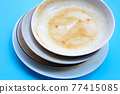 Dirty dishes on blue background. 77415085