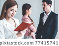Businesswoman reading book in business office . 77415741