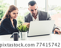 Businessman and businesswoman working in office. 77415742