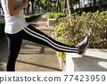 Asian girl stretch legs after running exercise 77423959