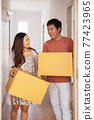 Couple carry box into new apartment or house 77423965