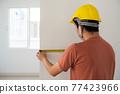 Interior engineer use measure tape at blank wall 77423966
