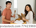 Couple unpack kitchen tools on box at new house 77423969