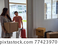 Couple carry luggage and moving box to new house 77423970