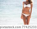 Tanned woman body in bikini 77425233
