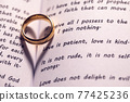 Golden wedding ring on bible book 77425236
