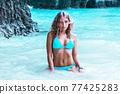 Woman in bikini on beach 77425283
