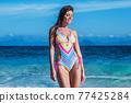 Woman in bikini at seaside 77425284