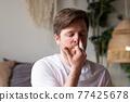 Caucasian mature man practicing yoga sitting, making Alternate Nostril Breathing 77425678