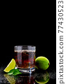 Whiskey with steel cooling cubes on dark glass background 77430523