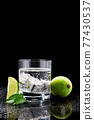 Glass of Soda or Coctail with steel cooling cubes on dark glass background 77430537