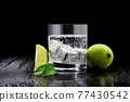 Glass of Soda or Coctail with steel cooling cubes on dark glass background 77430542