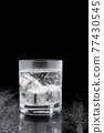 Glass of Soda or Coctail with steel cooling cubes on dark glass background 77430545