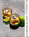 Whiskey with steel cooling cubes on dark glass background 77430570
