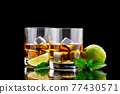 Whiskey with steel cooling cubes on dark glass background 77430571