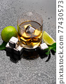 Whiskey with steel cooling cubes on dark glass background 77430573