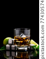 Whiskey with steel cooling cubes on dark glass background 77430574