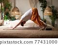 Young man practicing yoga at home doing downward facing asana 77431000