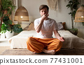 Caucasian mature man practicing yoga sitting, making Alternate Nostril Breathing 77431001