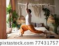 man practicing yoga doing warrior pose or virabhadrasana at home 77431757