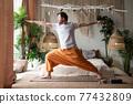 man practicing yoga doing warrior pose or virabhadrasana at home 77432809