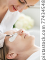 Cosmetician giving eyelash treatment to customer 77434548