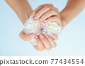 Female hands holding white flower 77434554