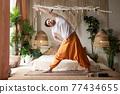 Caucasian man practicing yoga trikonasana pose at the living room 77434655