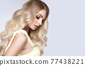 Beautiful blond girl with a perfectly curls hair, and classic make-up. Beauty face and hair. 77438221