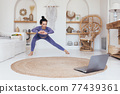 Woman working out at home watching an online class 77439361