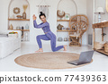 Woman exercising watching online videos on laptop, doing lunge exercises watching online exercise session on her laptop. 77439363