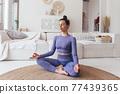 Woman meditating in lotus yoga position, practising yoga. 77439365