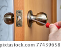 Joiner uses screwdriver to secure both handle sides to door. 77439658