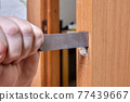 Using chisel, joiner cuts hole for door latch strip. 77439667