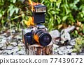 During forest fire, camera of tourists in tent city is burned. 77439672