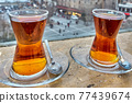 Two glasses of Turkish black tea sit on windowsill overlooking city. 77439674