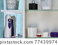 Oral irrigator and other personal hygiene items are located on shelves of wall cabinet in bathroom. 77439974